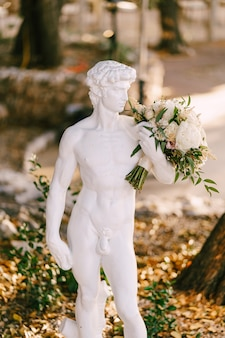 Greek antique sculpture of a young stately david with the bride's wedding bouquet.
