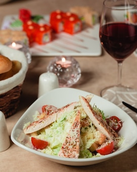 Greek caesar salad with white meat, lettuce and cherry tomatoes.