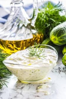 Греческий соус или заправка цацики, приготовленные из огурца, сметаны, йогурта, оливкового масла и свежего укропа