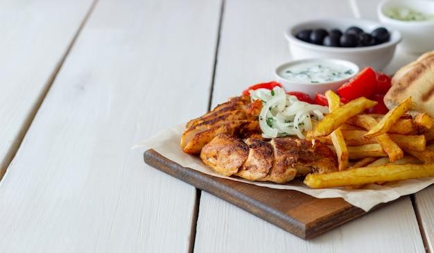 チキン、フライドポテト、トマト、玉ねぎ、ピタを添えたギリシャ料理のジャイロ。ギリシャ料理。