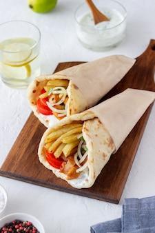 Гирос греческого блюда с курицей, картофелем фри, помидорами, луком и лавашем. греческая кухня.