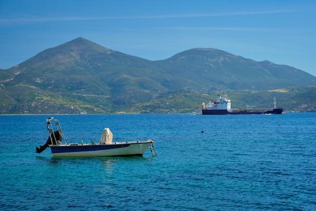 Греческий рыболовный скоростной катер и грузовое судно в эгейском море греция