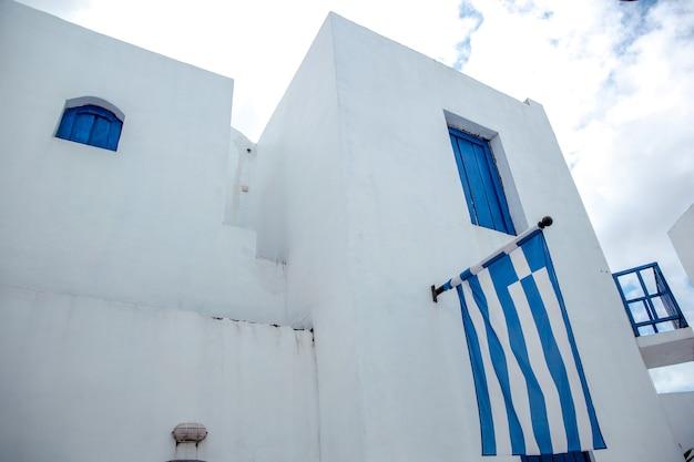 그리스 백색 전통 집에서 벽에 그리스 깃발
