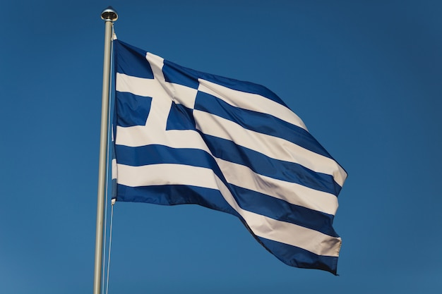 Greek flag with blue and white colours against sky background