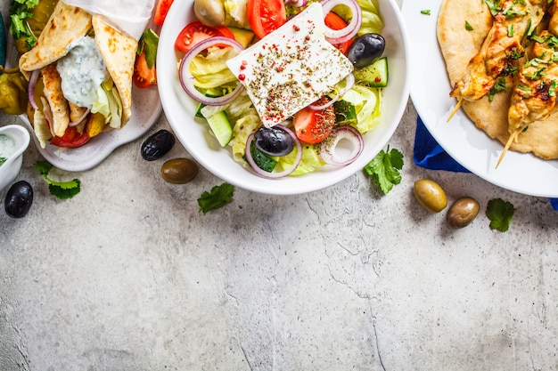 Greek food: greek salad, chicken souvlaki and gyro on gray background, top view, copy space. traditional greek cuisine concept.