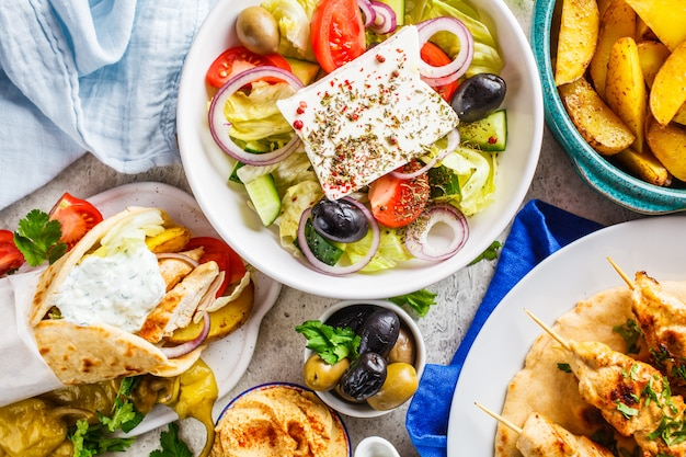 Greek food: greek salad, chicken souvlaki, gyros and baked potato wedges on gray background, top view. traditional greek cuisine concept.