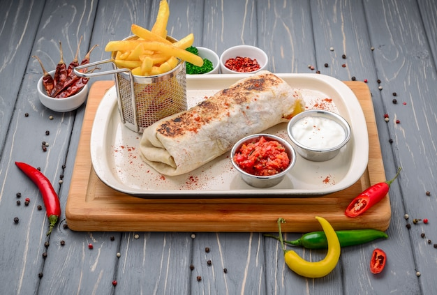 Greek gyro wrap cut in halfnd served with fries