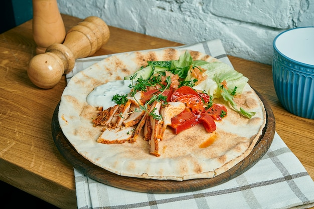 Greek gyros with yogurt, chicken, cucumber and tomatoes on a wooden table. street food