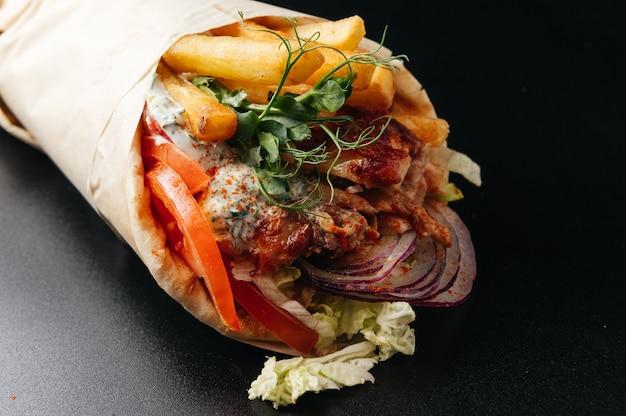 黒の背景にピタパンに包まれたギリシャのジャイロジャイロピタシャワルマは屋台の食べ物を奪う