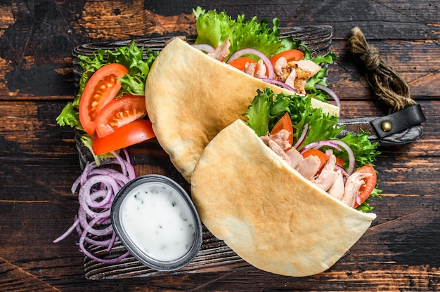 Greek gyros wrapped in pita breads with vegetables and sauce on wooden table. top view.
