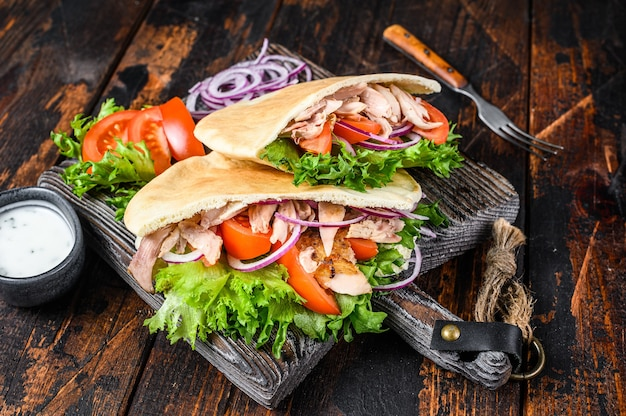 Greek gyros wrapped in pita breads with vegetables and sauce.
