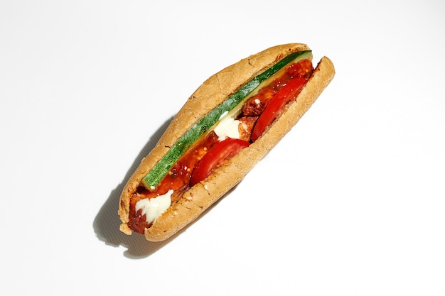 Greek hot dog with souvlaki, red sauce, tomatoes and cucumber. street food, hard light. white surface
