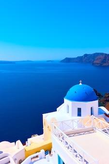 그리스 산토리니(santorini)의 이아(oia)에 파란색 돔과 바다가 있는 그리스 정교회 - 풍경, 텍스트 공간