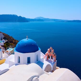 그리스 산토리니 섬의 이아 작은 마을에 있는 바다 옆에 파란색 돔이 있는 그리스 정교회 - 풍경
