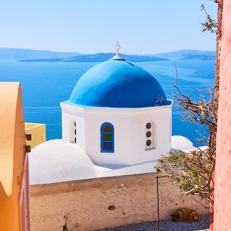 그리스 산토리니 섬의 이아 마을에 있는 바다 옆에 파란색 돔이 있는 그리스 정교회