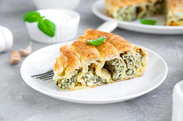 Греческий пирог спанакопита с сыром фета и шпинатом на белой тарелке