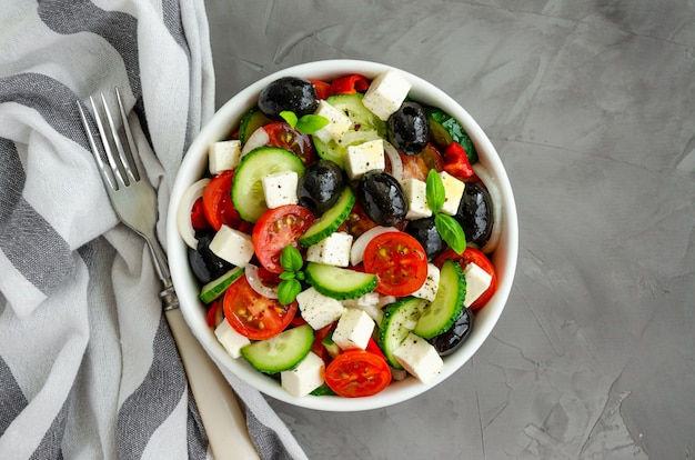 Greek salad of fresh juicy vegetables, feta cheese, herbs and olives in a white bowl on a dark concrete background. healthy food. horizontal orientation. top view.