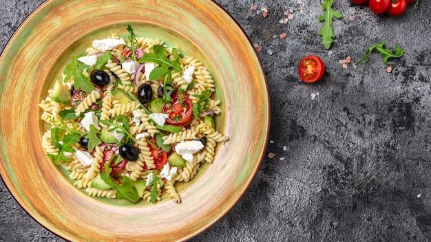 Греческий салат, свежая паста. средиземноморская кухня. баннер, меню, рецепт. здоровая пища. вид сверху