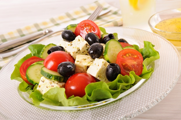 Greek salad in glass bowl with sauce