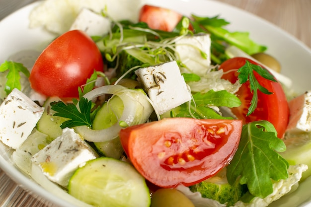 Greek salad or horiatiki with large pieces of tomatoes, cucumbers, feta cheese and micro greens sprouts closeup. village salad with diced mozzarella, arugula, spices and olive oil