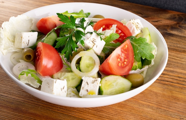 Greek salad or horiatiki with large pieces of tomatoes, cucumbers, onion, feta cheese and olives in white bowl closeup. village salad with diced mozzarella, arugula, parsley, spices and olive oil