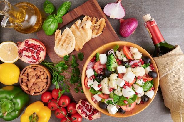 Insalata greca o horiatiki con grandi pezzi di pomodori, cetrioli, cipolla, formaggio feta e olive in vista dall'alto isolato ciotola bianca. insalata di paese con mozzarella a dadini, rucola, prezzemolo e olio d'oliva