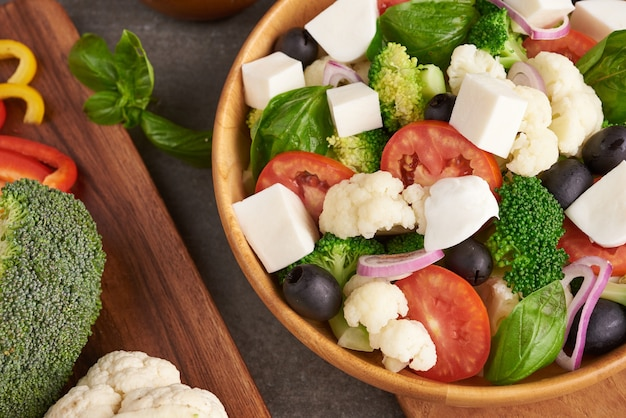 Greek salad or horiatiki with large pieces of tomatoes, cucumbers, onion, feta cheese and olives in white bowl isolated top view. village salad with diced mozzarella, arugula, parsley and olive oil