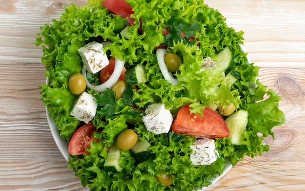 Greek salad or horiatiki with large pieces of tomatoes, cucumbers, onion, feta cheese and olives in white bowl top view. green village salad with diced mozzarella, lettuce, spices and olive oil
