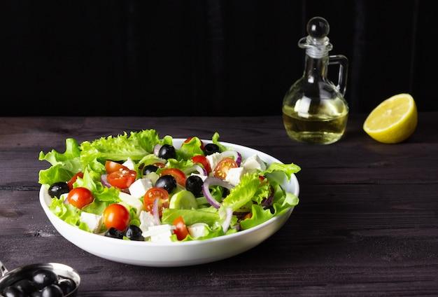 어두운 배경에 접시에 그리스 샐러드. 건강한 채식 음식. 죽은 태아의 치즈, 양상추 잎, 방울 토마토.