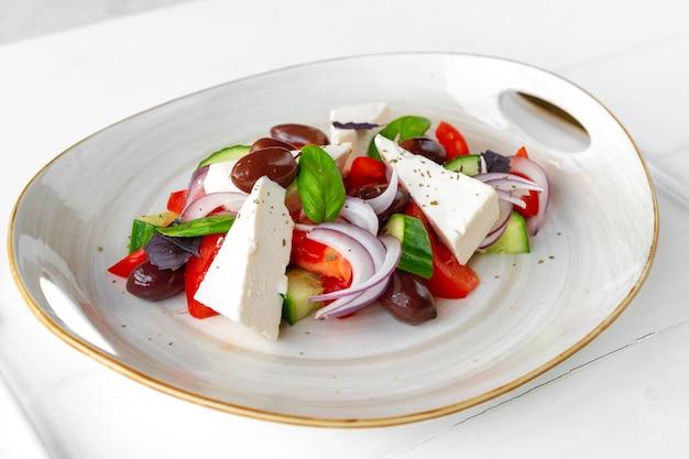 Греческий салат в тарелке на белом деревянном фоне