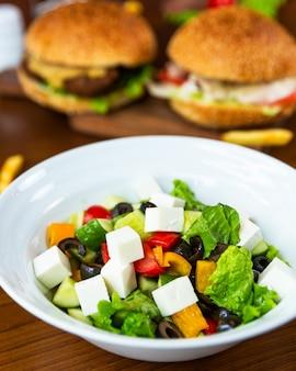 ハンバーガーと白いプレートのギリシャ風サラダ