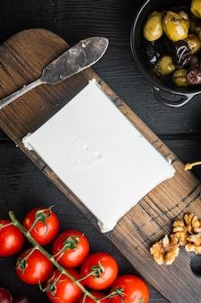 ギリシャ風サラダの主な材料、新鮮なオリーブミックス、フェタチーズ、トマト、黒い木製のテーブル、上面図
