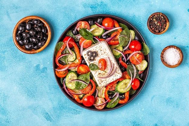 新鮮なキュウリ、トマト、ピーマン、赤玉ねぎ、フェタチーズ、オリーブのギリシャ風サラダ