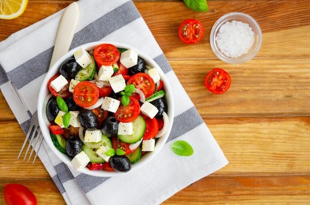 Греческий салат из свежих сочных овощей, сыра фета, зелени и оливок в белой миске. здоровая пища.