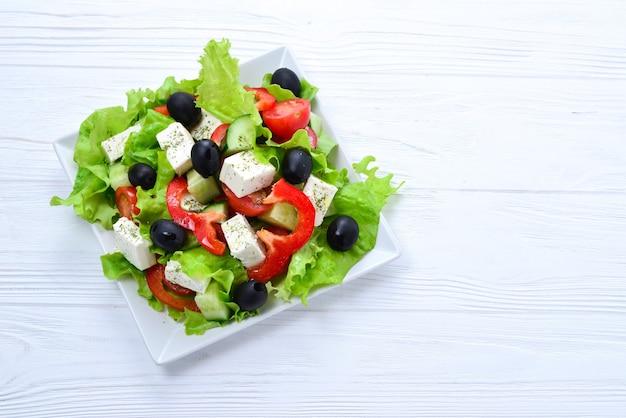 Греческий салат на белом фоне деревянных. место для текста или дизайна.