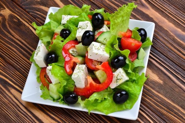 Греческий салат на деревянном фоне. место для текста или дизайна.