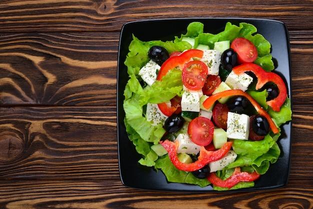 木製の背景にギリシャ風サラダ