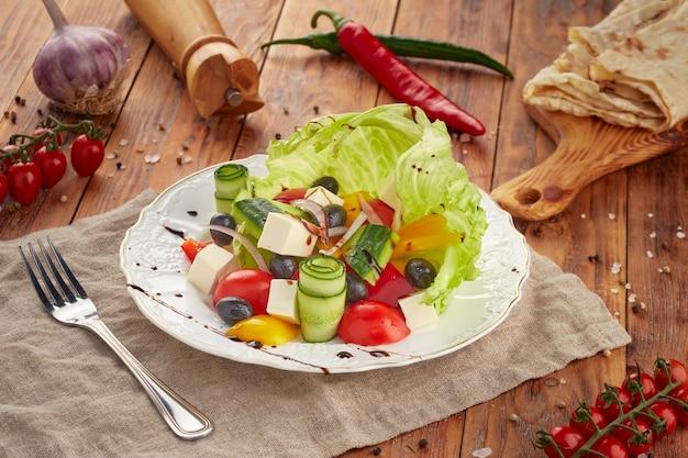 Греческий салат на деревянных фоне, вегетарианская еда