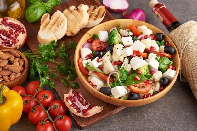 大きなトマト、きゅうり、玉ねぎ、フェタチーズ、オリーブを白いボウルに入れたギリシャ風サラダまたはホリアティキ。さいの目に切ったモッツァレラチーズ、ルッコラ、パセリ、オリーブオイルのビレッジサラダ