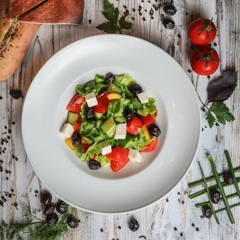 Insalata greca in un piatto con pomodoro, olive, pane, erbe e spezie