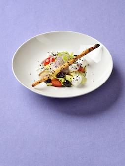 ギリシャ風サラダバイオレットリネンの背景にゴマブレッドスティックを添えて