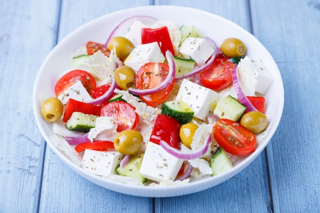 Греческий салат. традиционное греческое блюдо. здоровое вегетарианское питание. свежие овощи и сыр фета в белой тарелке. крупный план, синий фон.