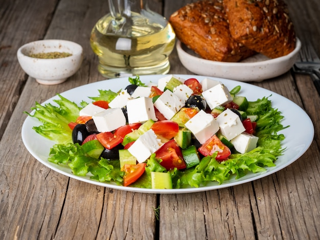 Greek salad on white plate on old rustic wooden table, side view