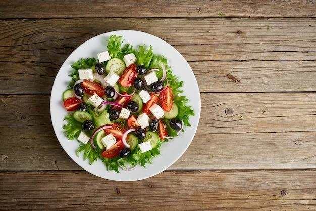 Greek salad on white plate on old rustic wooden table, top view, copy space