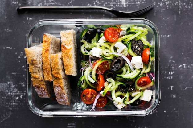 Greek salad with bread in a glass container