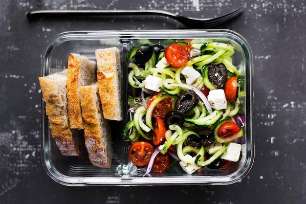 Греческий салат с хлебом в стеклянной посуде