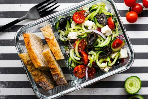 유리 용기에 빵과 그리스 샐러드