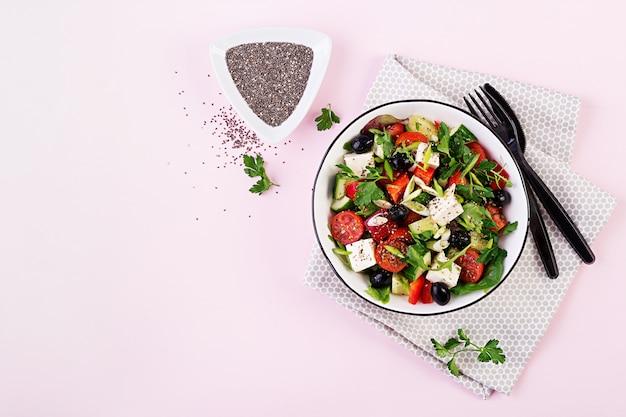 Греческий салат с огурцом, помидорами, сладким перцем, листьями салата, зеленым луком, сыром фета и оливками с оливковым маслом. здоровая пища. вид сверху