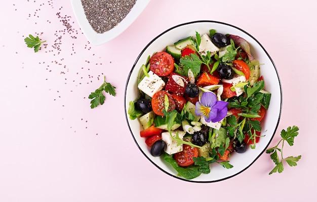 キュウリ、トマト、ピーマン、レタス、ネギ、フェタチーズ、オリーブオイルとオリーブのギリシャ風サラダ。健康食品。上面図