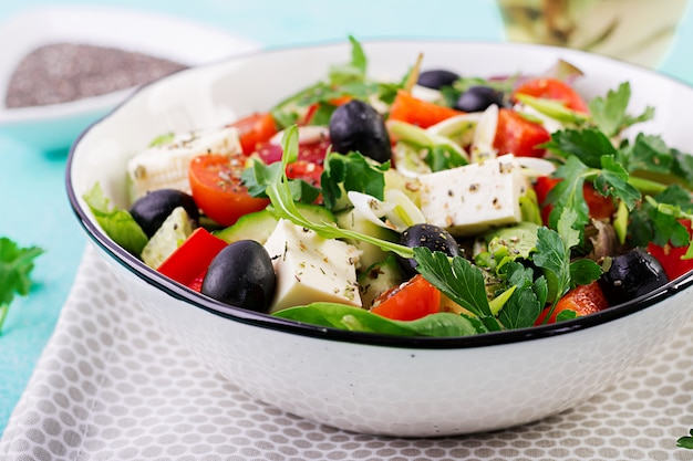 Greek salad  with cucumber, tomato, sweet pepper, lettuce, green onion, feta cheese and olives with olive oil. healthy food.